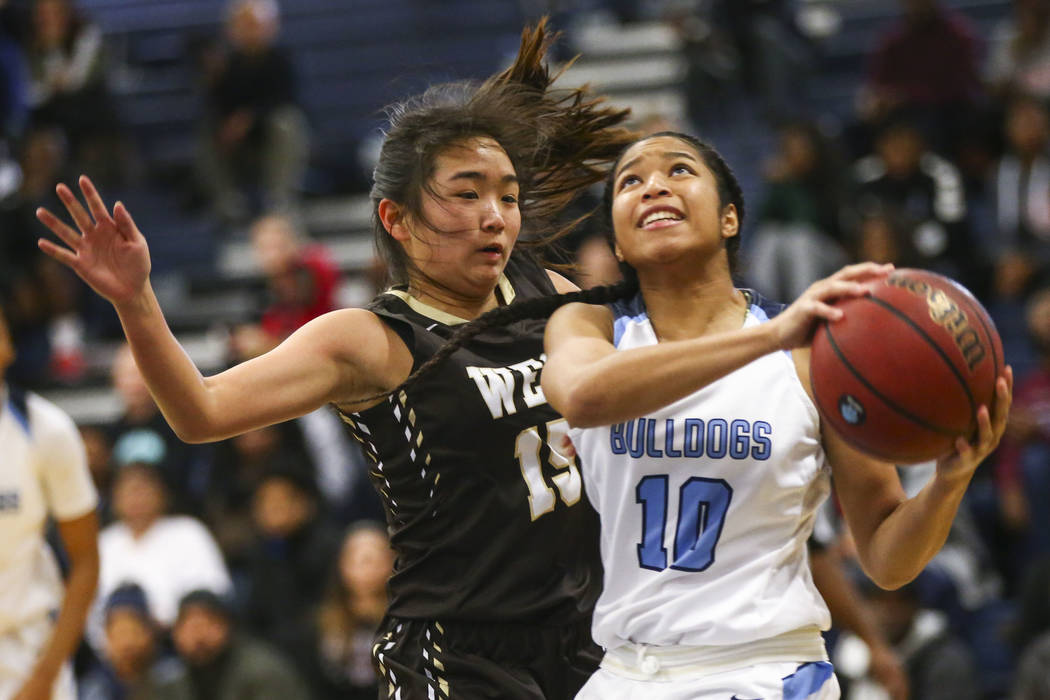 Centennial's Ajanhai Phoumiphat (10) goes to the basket against West's Rachel Arakawa (15) while drawing a foul during a basketball game at Centennial High School in Las Vegas on Sat ...