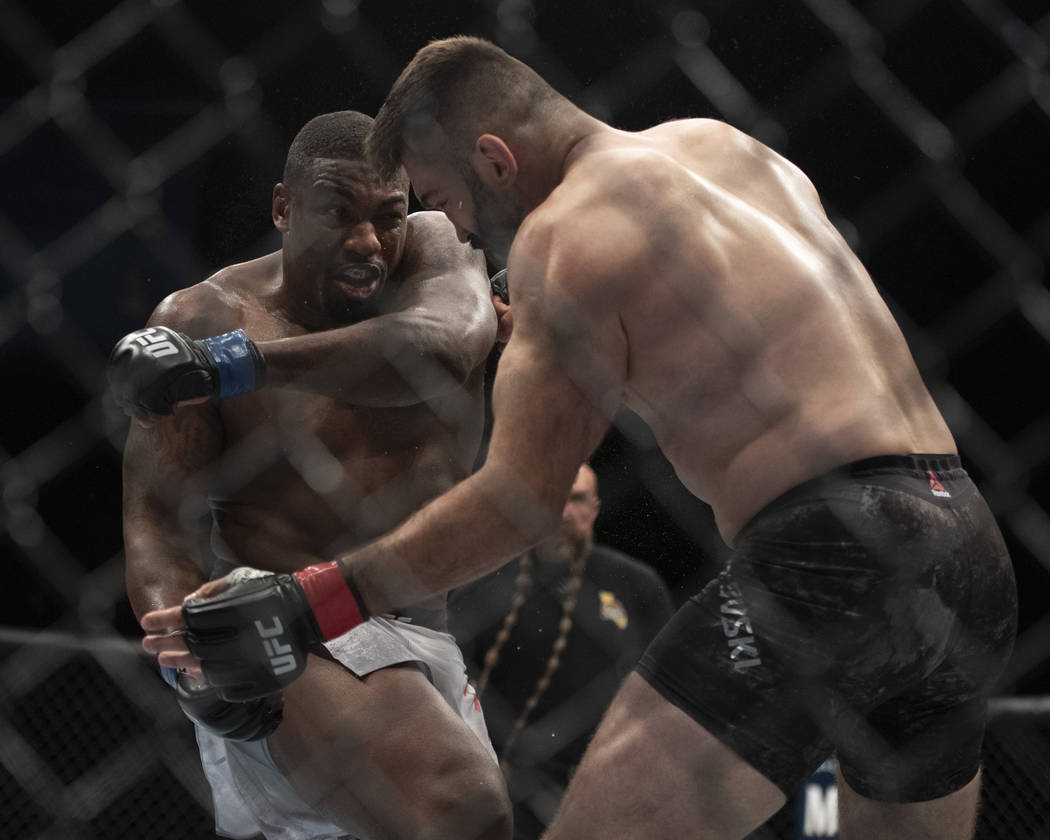 Walt Harris, left, follows through on a punch to Andrei Arlovski during the first round of a heavyweight mixed martial arts bout at UFC 232, Saturday, Dec. 29, 2018, in Inglewood, Calif. (AP Photo ...