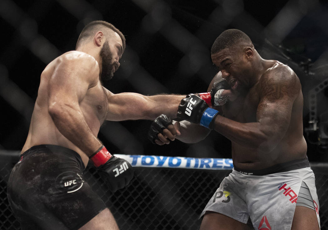 Andrei Arlovski, left, lands a punch to Walt Harris during the first round of a heavyweight mixed martial arts bout at UFC 232, Saturday, Dec. 29, 2018, in Inglewood, Calif. (AP Photo/Kyusung Gong)
