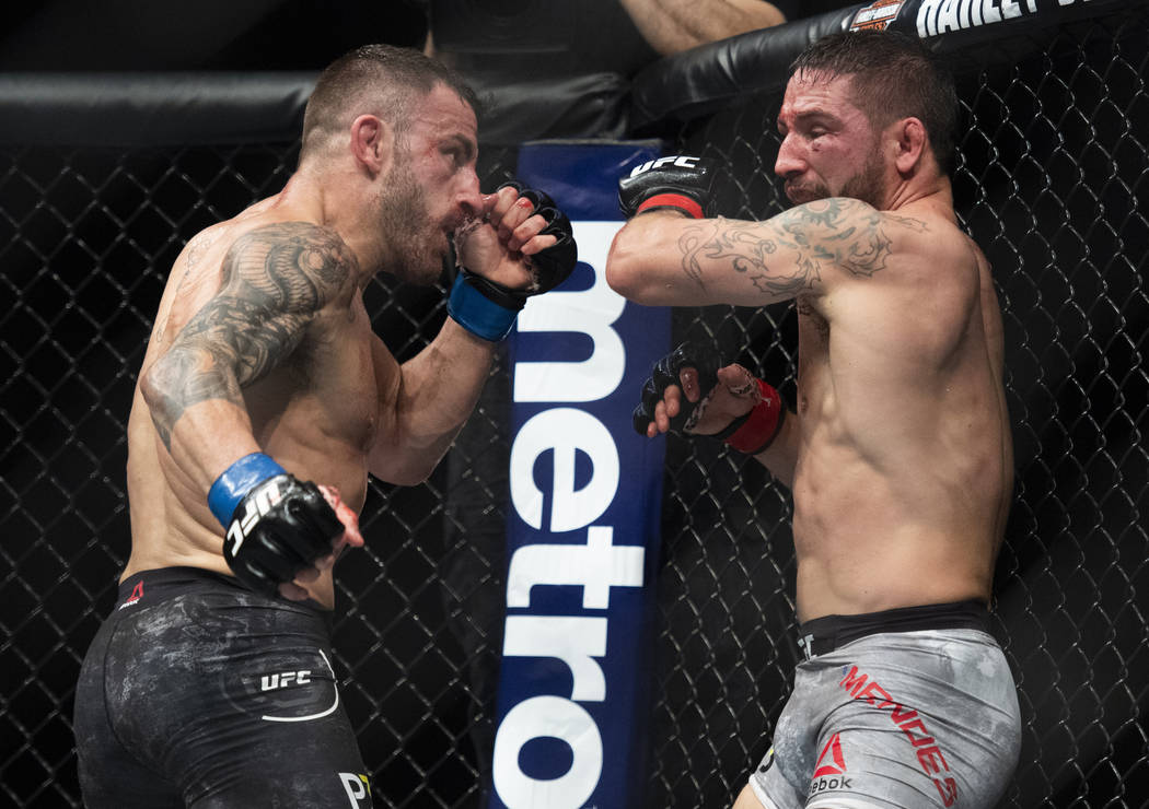 Alexander Volkanovski, left, and Chad Mendes square off during the second round of a featherweight mixed martial arts bout at UFC 232, Saturday, Dec. 29, 2018, in Inglewood, Calif. (AP Photo/Kyusu ...