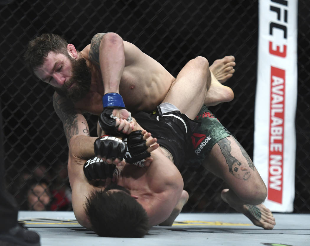 Michael Chiesa, top, throws a punch to Carlos Condit during the first round of a welterweight mixed martial arts bout at UFC 232, Saturday, Dec. 29, 2018, in Inglewood, Calif. (AP Photo/Kyusung Gong)