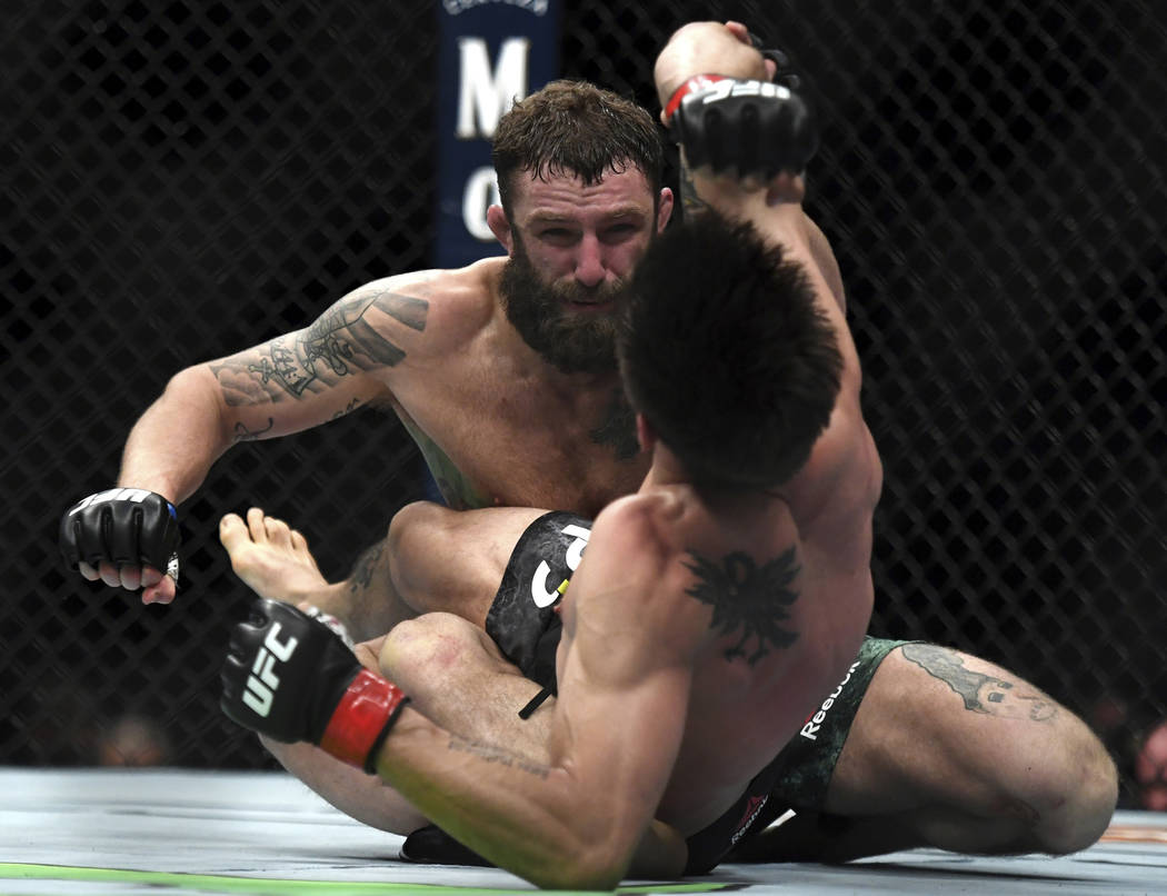 Michael Chiesa, back, throws a punch to Carlos Condit during the first round of a welterweight mixed martial arts bout at UFC 232, Saturday, Dec. 29, 2018, in Inglewood, Calif. (AP Photo/Kyusung Gong)