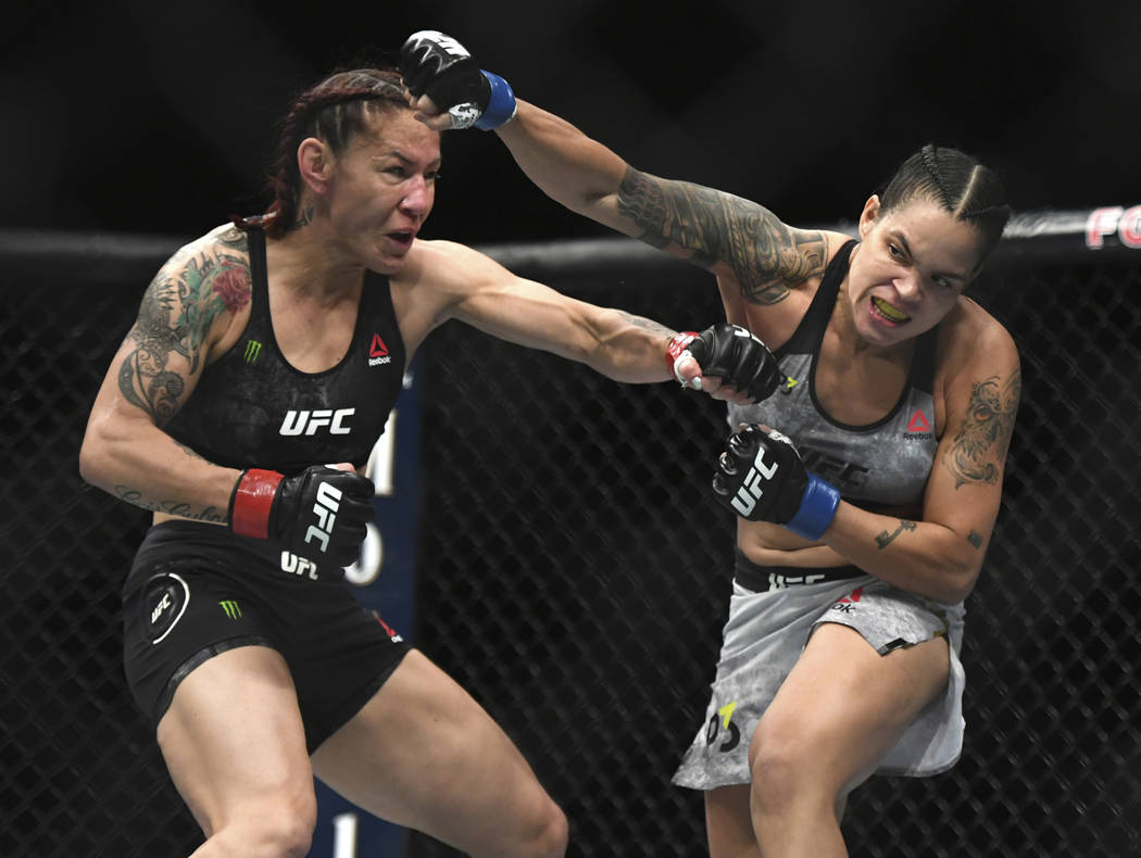 Amanda Nunues, right, throws a punch to Cris Cyborg during the first round of a featherweight title mixed martial arts bout at UFC 232, Saturday, Dec. 29, 2018, in Inglewood, Calif. (AP Photo/Kyus ...
