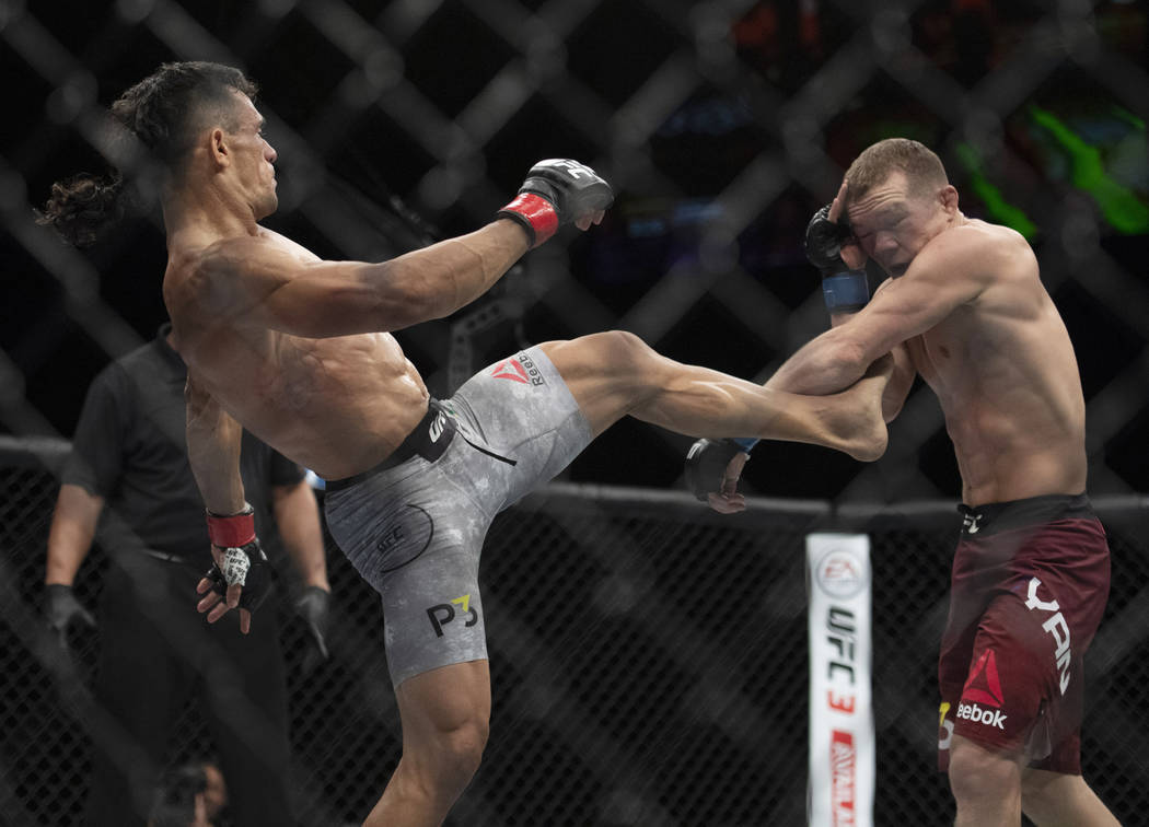 Douglas Silva de Andrade, left, lands a kick to Petr Yan during the second round of a bantamweight mixed martial arts bout at UFC 232, Saturday, Dec. 29, 2018, in Inglewood, Calif. (AP Photo/Kyusu ...