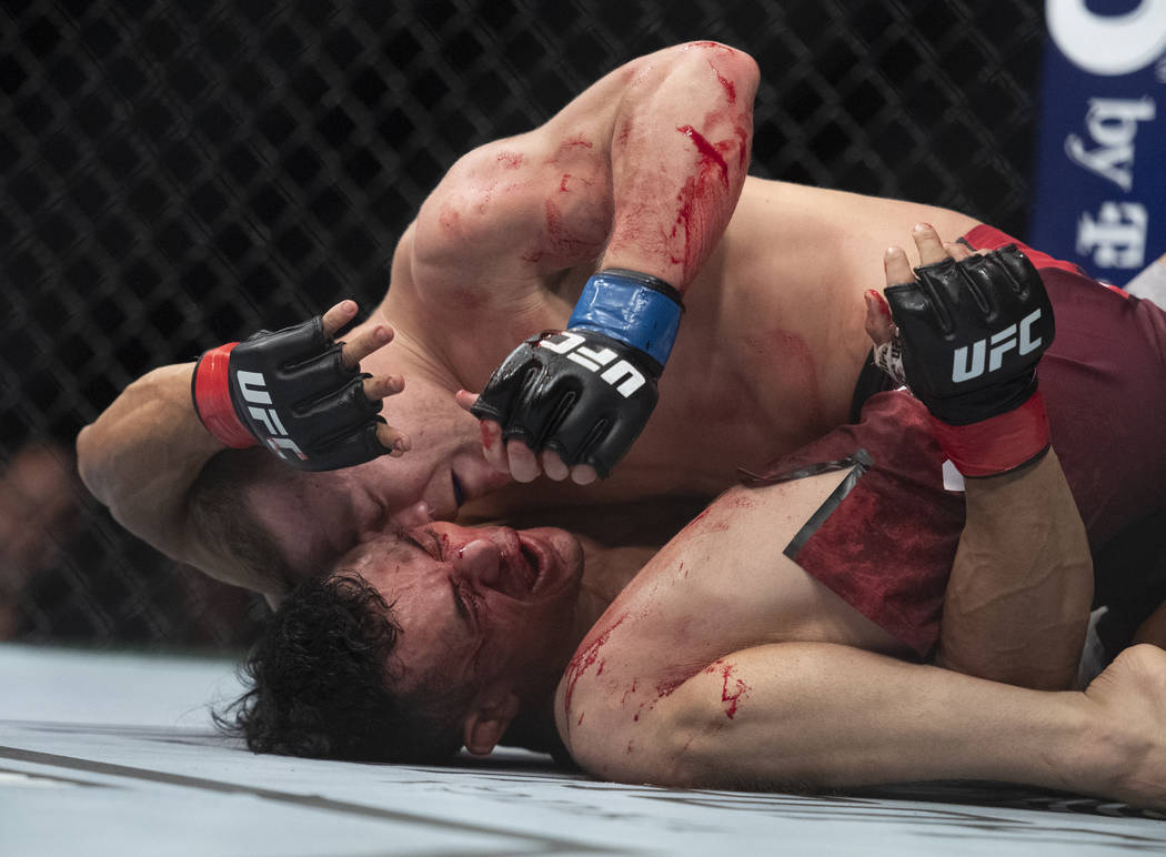 Petr Yan, top, hits Douglas Silva de Andrade during the second round of a bantamweight mixed martial arts bout at UFC 232, Saturday, Dec. 29, 2018, in Inglewood, Calif. (AP Photo/Kyusung Gong)