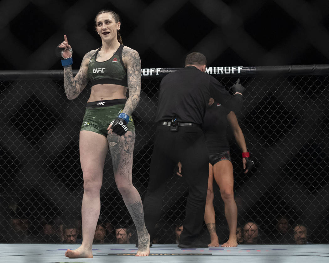 Megan Anderson, left, smiles after defeating Cat Zingano in a featherweight mixed martial arts bout at UFC 232, Saturday, Dec. 29, 2018, in Inglewood, Calif. (AP Photo/Kyusung Gong)
