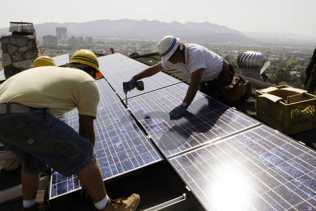 In this March 23, 2010, file photo, workers from California Green Design install solar electrical panels on the roof of a home in Glendale, Calif. (AP Photo/Reed Saxon, File)