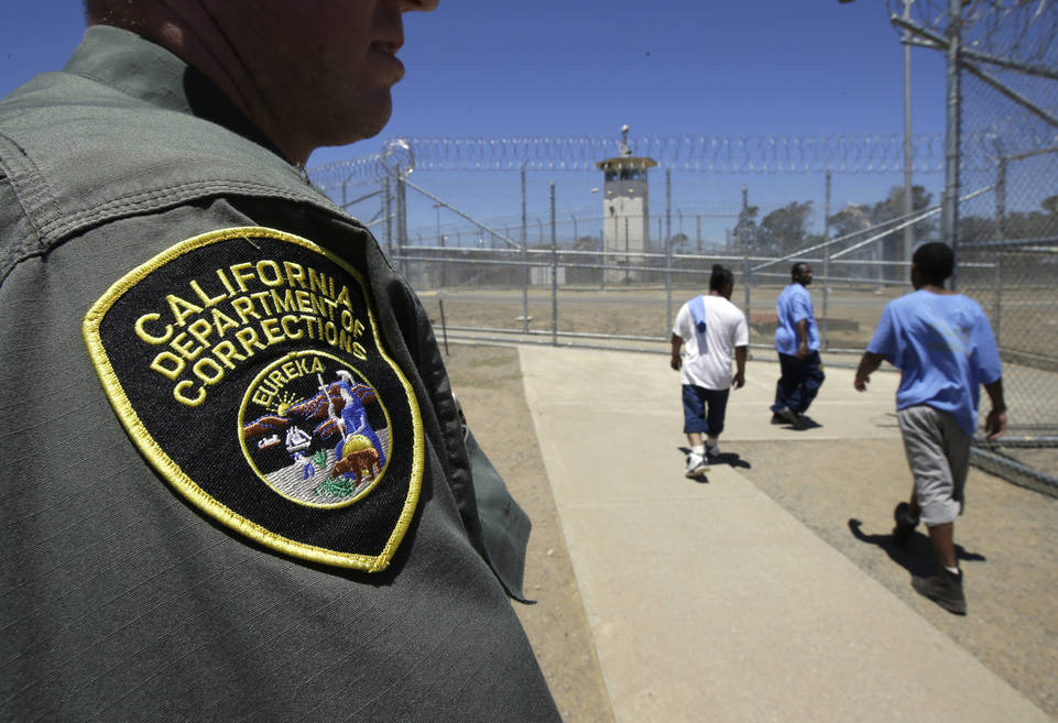 In this June 20, 2018 file photo, inmates pass a correctional officer as they leave an exercise yard at the California Medical Facility in Vacaville, Calif. (AP Photo/Rich Pedroncelli, File)