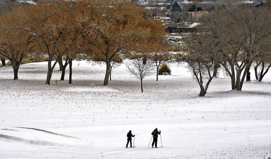 Morgan Edwards-Fligner and Gavin Hall cross country ski through the Arroyo del Oso golf course in Albuquerque as a severe winter storm hits New Mexico on Friday, Dec. 27, 2018. (Jim Thompson/The A ...