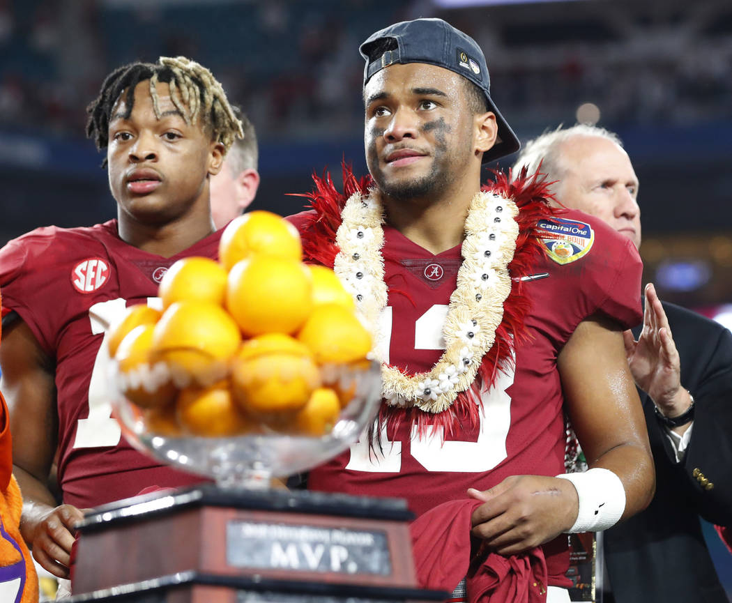 Alabama quarterback Tua Tagovailoa (13) stands next to the MVP trophy for the offensive player of the game at the end of the Orange Bowl NCAA college football game against Oklahoma , Sunday, Dec. ...