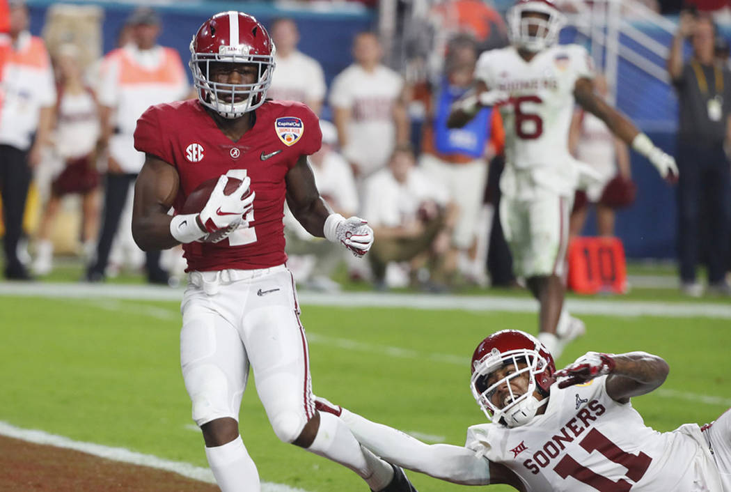 Alabama wide receiver Jerry Jeudy (4) scores a touchdown ahead of a takle by Oklahoma cornerback Parnell Motley (11), during the second half of the Orange Bowl NCAA college football game, Saturday ...