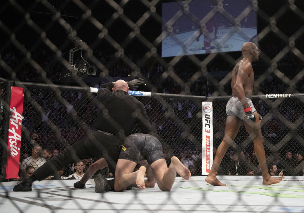 Jon Jones walks away from Alexander Gustafsson at the end of their UFC men's light heavyweight mixed martial arts bout at UFC 232, Saturday, Dec. 29, 2018, in Inglewood, Calif. (AP Photo/Kyusung Gong)