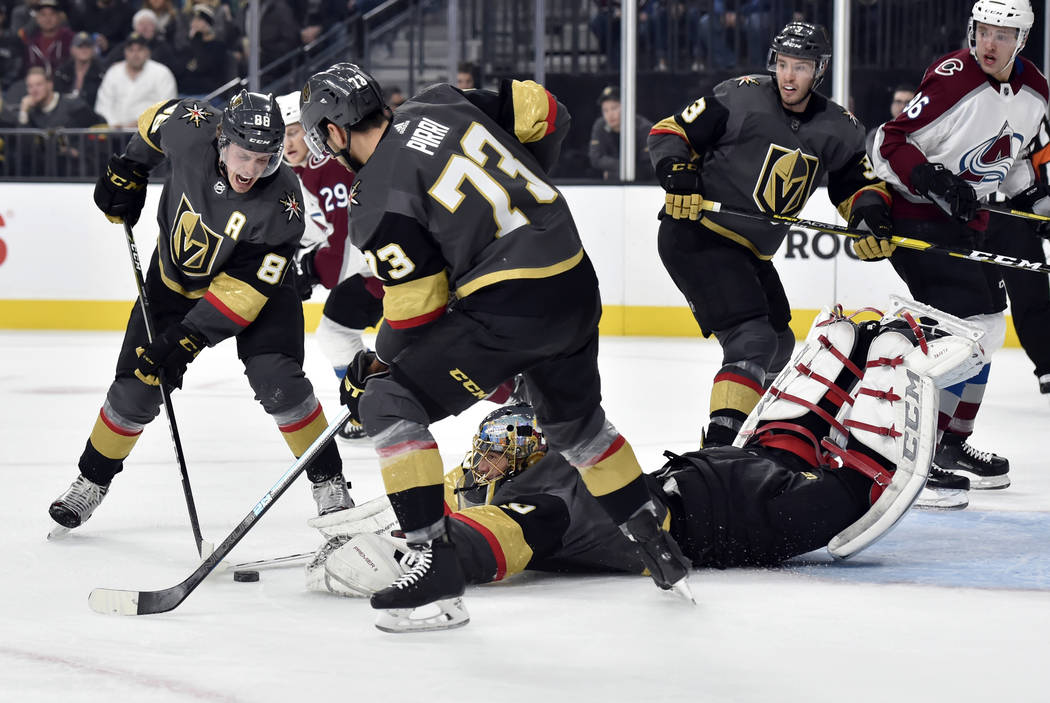 Vegas Golden Knights goaltender Marc-Andre Fleury (29) dives for the puck with Nate Schmidt (88) and Brandon Pirri (73) defending against the Colorado Avalanche during the first period of an NHL h ...