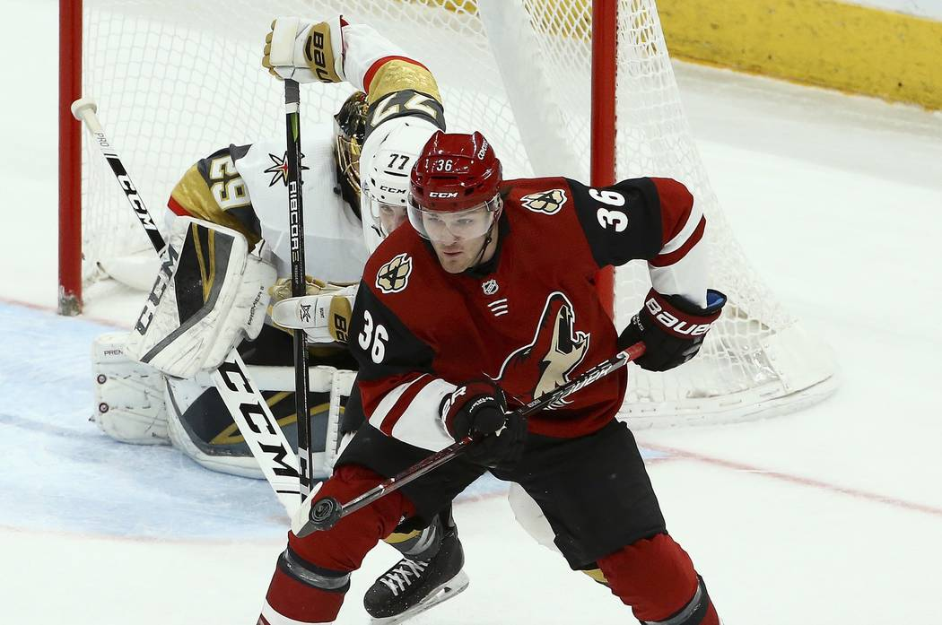 Arizona Coyotes right wing Christian Fischer (36) catches the puck with his stick as Vegas Golden Knights defenseman Brad Hunt (77) closes in during the third period of an NHL hockey game Sunday, ...