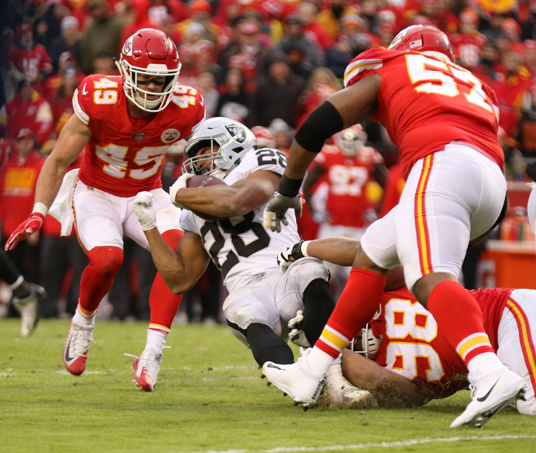 Oakland Raiders running back Doug Martin (28) fights for more yards as Kansas City Chiefs nose tackle Xavier Williams (98) tackles him during the first half of an NFL game in Kansas City, Mo., Sun ...