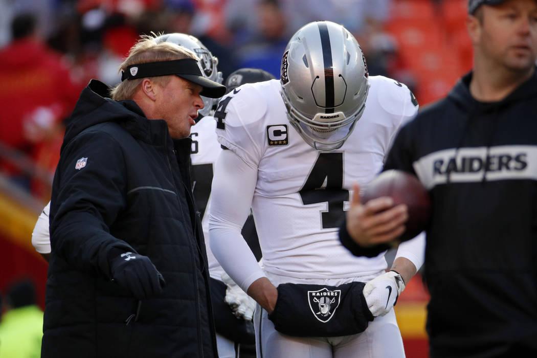 Oakland Raiders head coach Jon Gruden talks to quarterback Derek Carr (4) before an NFL football game against the Kansas City Chiefs in Kansas City, Mo., Sunday, Dec. 30, 2018. (AP Photo/Charlie R ...