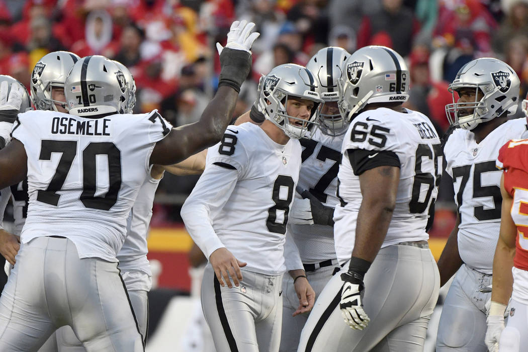 Oakland Raiders kicker Daniel Carlson (8) is congratulated by teammates after he kicked a field goal during the first half of an NFL football game against the Kansas City Chiefs in Kansas City, Mo ...