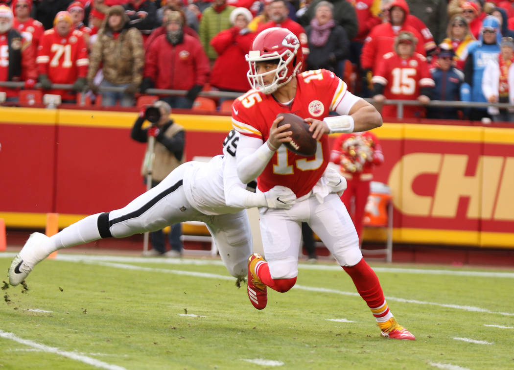Kansas City Chiefs quarterback Patrick Mahomes (15) sheds a tackle by Oakland Raiders outside linebacker Tahir Whitehead (59) during the first half of an NFL game in Kansas City, Mo., Sunday, Dec. ...
