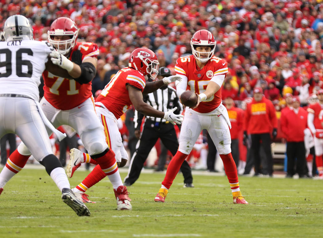 Kansas City Chiefs quarterback Patrick Mahomes (15) hands off the football to running back Darrel Williams (31) during the first half of an NFL game against the Oakland Raiders in Kansas City, Mo. ...