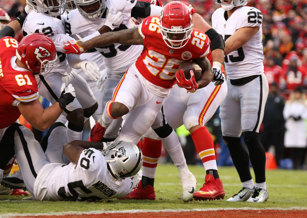 Kansas City Chiefs running back Damien Williams (26) breaks a tackle from Oakland Raiders linebacker Nicholas Morrow (50) en route to scoring a touchdown during the first half of an NFL game in Ka ...