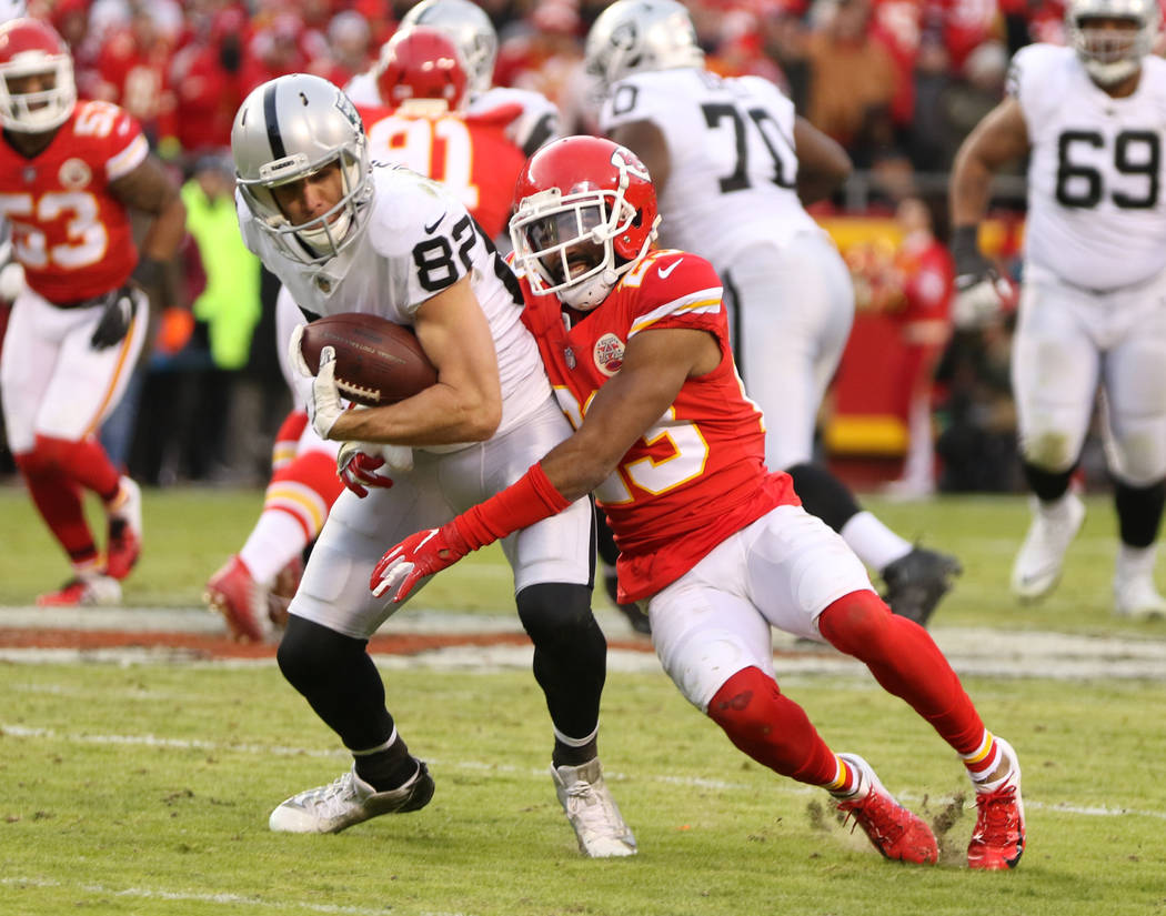 Kansas City Chiefs cornerback Kendall Fuller (23) tries to bring down Oakland Raiders wide receiver Jordy Nelson (82) during the first half of an NFL game in Kansas City, Mo., Sunday, Dec. 30, 201 ...