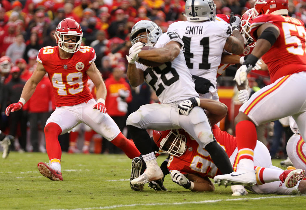 Oakland Raiders running back Doug Martin (28) fights for more yards as Kansas City Chiefs nose tackle Xavier Williams (98) tries to tackle him during the first half of an NFL game in Kansas City, ...