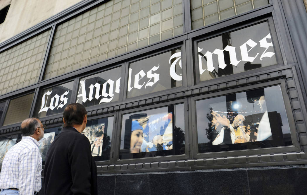In this May 16, 2016, file photo, pedestrians look at news photos posted outside the Los Angeles Times building in downtown Los Angeles. (AP Photo/Richard Vogel, File)