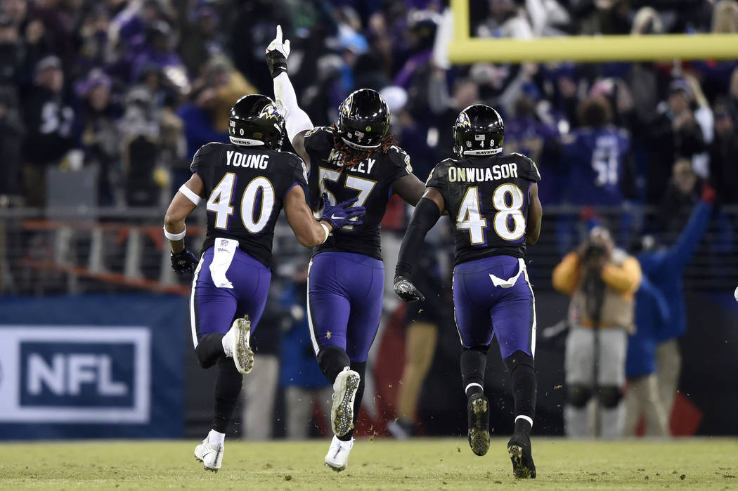 Baltimore Ravens inside linebacker C.J. Mosley, center, celebrates his interception with teammates Kenny Young, left, and Patrick Onwuasor in the second half of an NFL football game against the Cl ...