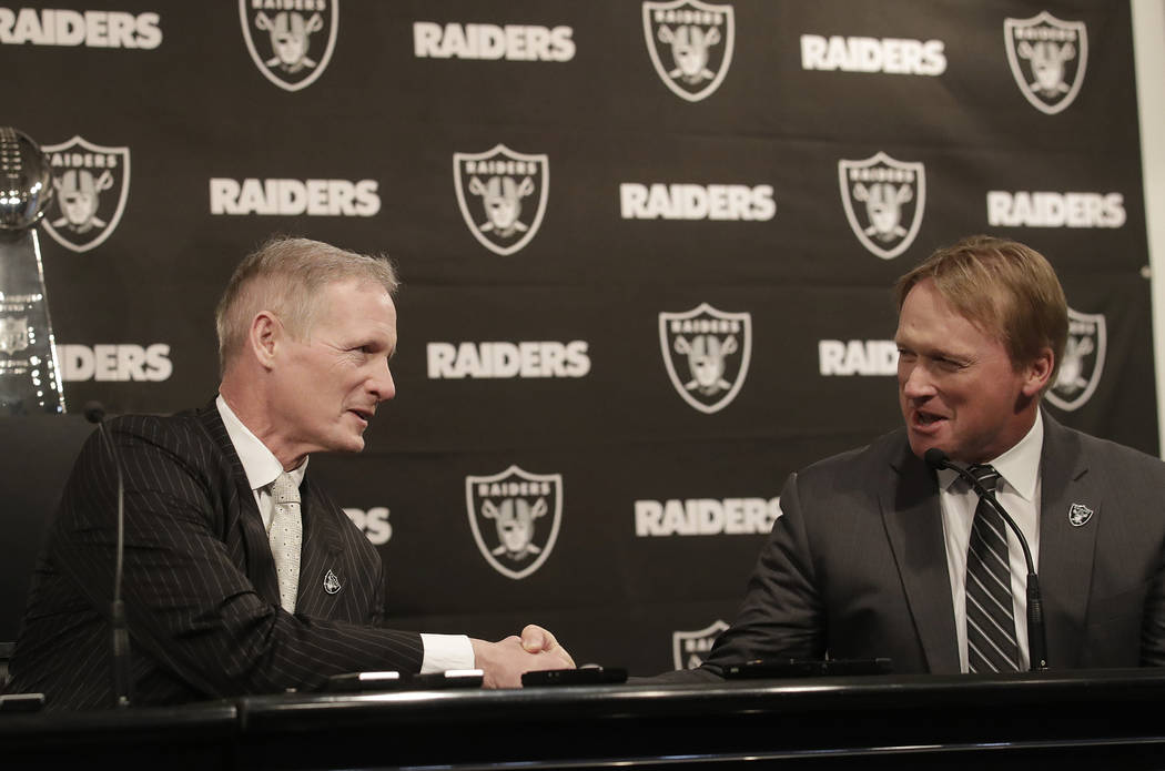 Mike Mayock, left, shakes hands with Oakland Raiders head coach Jon Gruden at a news conference announcing Mayock as the team's general manager in Oakland, Calif., Monday, Dec. 31, 2018. (AP Photo ...