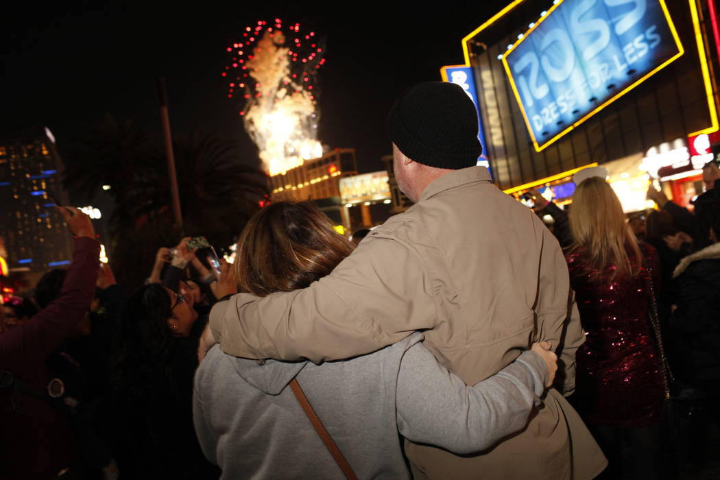 Suzie Gray, 50, left, and Steve Walker of Las Vegas watch fireworks on the Las Vegas Strip during the first minutes of New Year's Day, Jan. 1, 2018. (Joel Angel Juarez/Las Vegas Review-Journal) @j ...