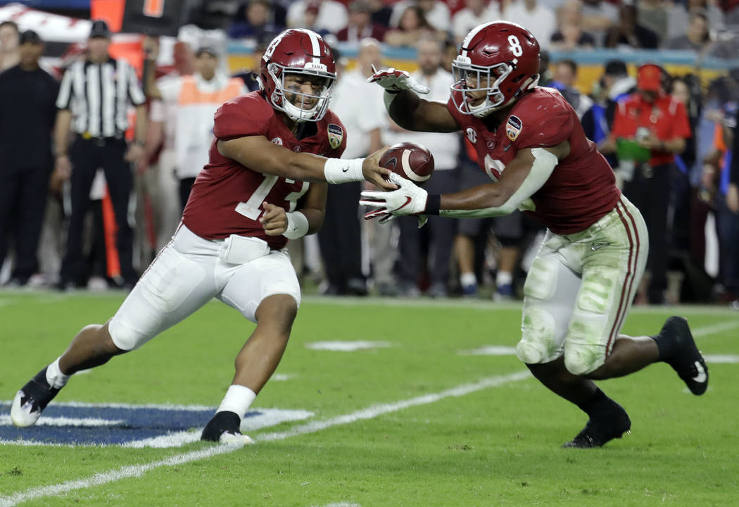 Alabama quarterback Tua Tagovailoa (13) hands the ball to Alabama running back Josh Jacobs (8), during the second half of the Orange Bowl NCAA college football game against Oklahoma, Saturday, Dec ...