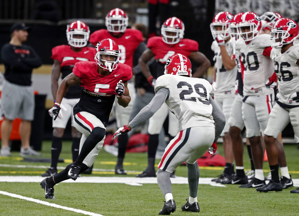 Georgia wide receiver Terry Godwin (5) goes through drills against defensive back Christopher Smith (29) during practice at the Superdome in New Orleans, Friday, Dec. 28, 2018. Georgia will face T ...