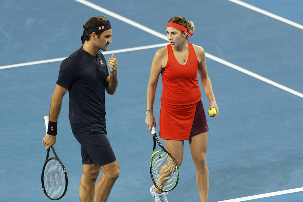 Roger Federer and Belinda Bencic of Switzerland talk during their mixed doubles match against Cameron Norrie and Katie Boulter of Great Britain at the Hopman Cup in Perth, Australia, Sunday Dec. 3 ...