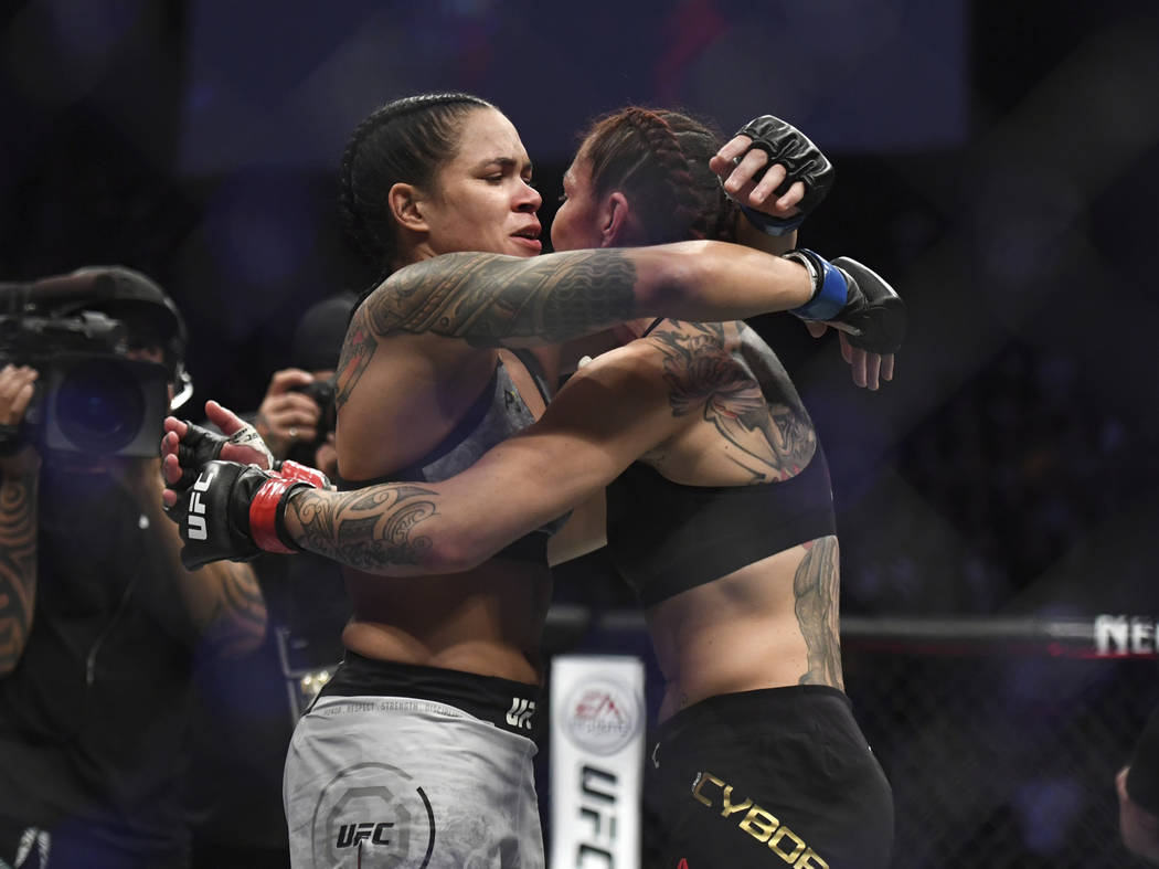 Amanda Nunes, left, and Cris Cyborg embrace each other after Nunes defeated Cyborg in the UFC women's featherweight mixed martial arts bout at UFC 232, Saturday, Dec. 29, 2018, in Inglewood, Calif ...