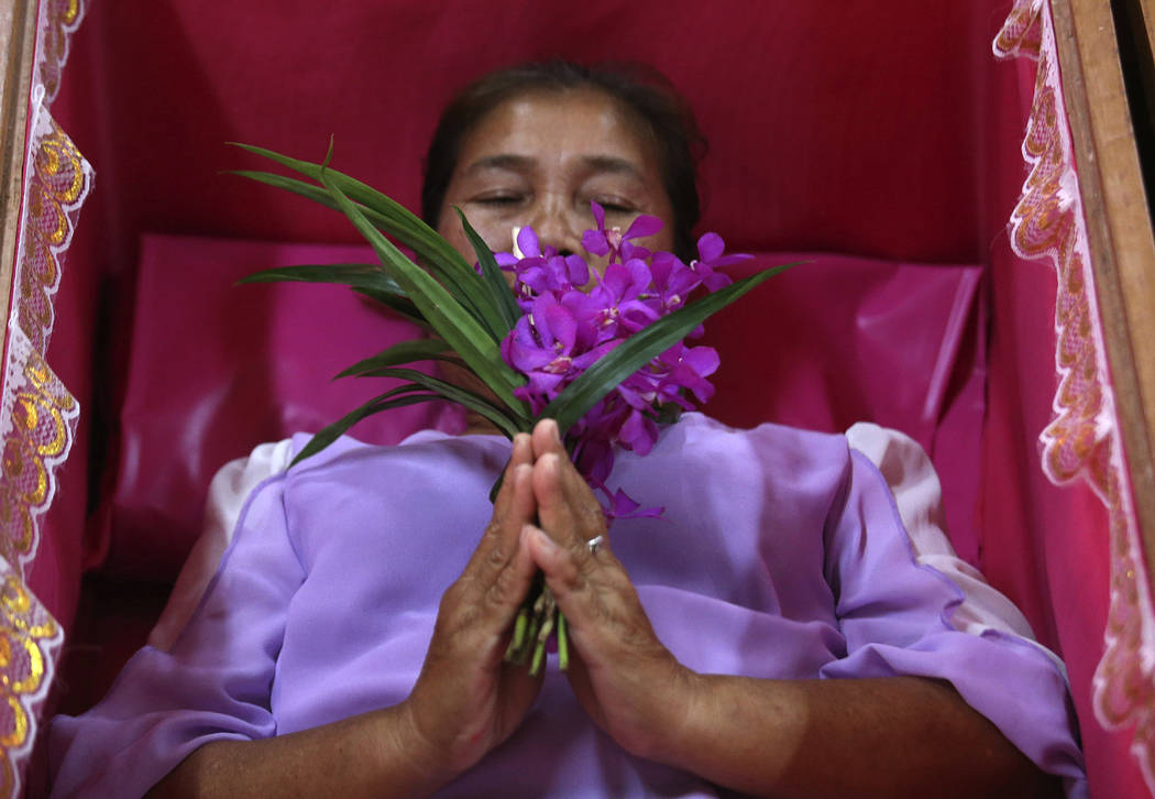 A worshipper prays as she takes her turn lying in a coffin at the Takien temple in suburban Bangkok, Thailand Monday, Dec. 31, 2018. Worshippers believe that the coffin ceremony – symbolizing de ...