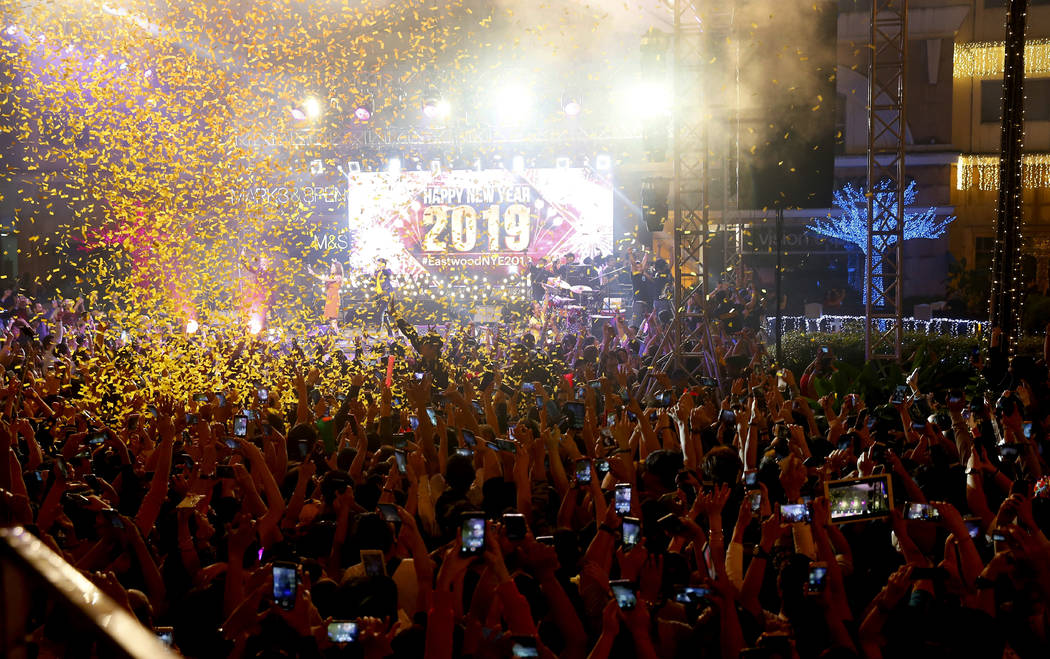 Confetti rains down on revelers at the Eastwood Shopping Mall as Filipinos welcome the New Year Tuesday, Jan. 1, 2019, in suburban Quezon city northeast of Manila, Philippines. Filipinos welcome t ...