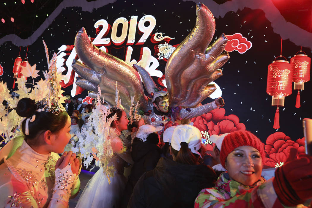 Performers take selfies at the end of a countdown to the new year event in Beijing, China, Tuesday, Jan. 1, 2019. (Ng Han Guan/AP)
