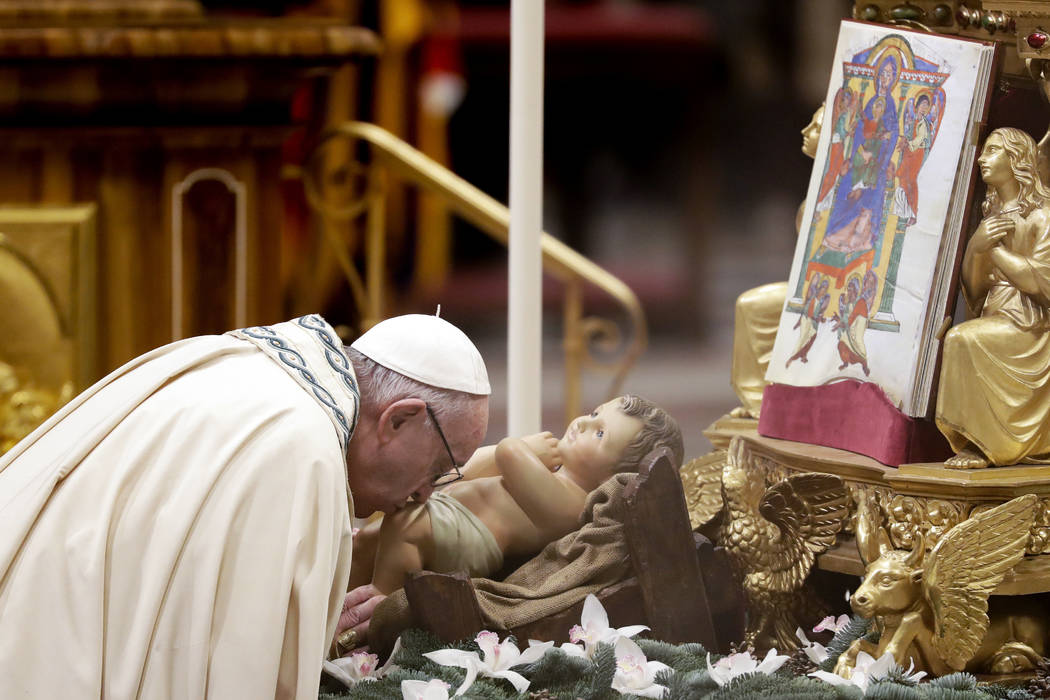 Pope Francis kisses a statue of Baby Jesus as he celebrates a new year's eve vespers Mass in St. Peter's Basilica at the Vatican, Monday, Dec. 31, 2018. (Andrew Medichini/AP)