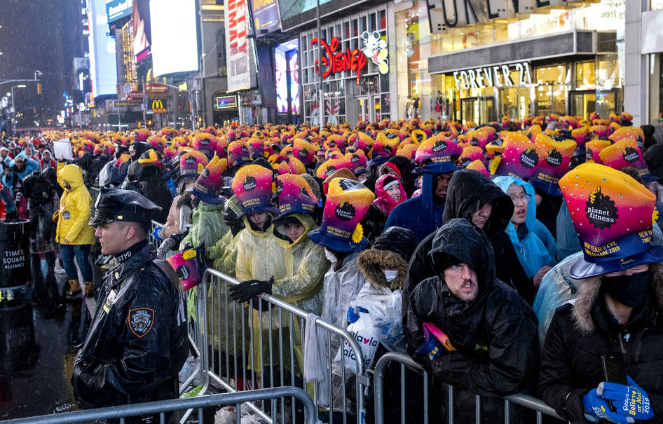 A New York City police officer stands near revelers gathered at Times Square in New York, Monday, Dec. 31, 2018, as they take part in a New Year's Eve celebration. (AP Photo/Craig Ruttle)