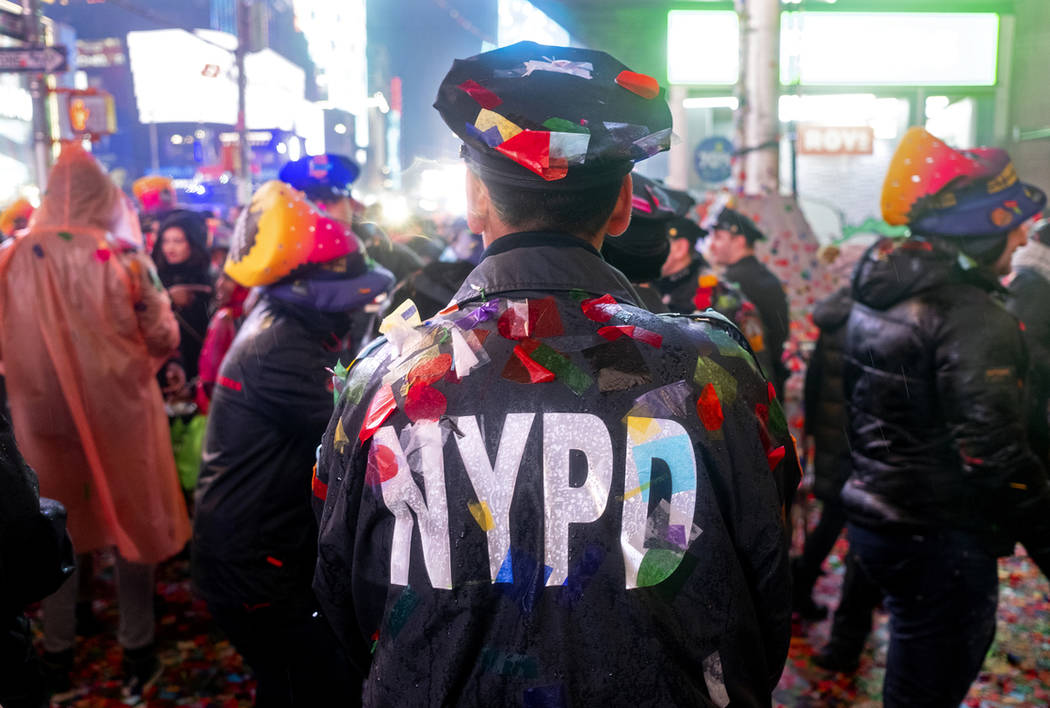A New York City police officer is covered with confetti in Times Square in New York, Tuesday, Jan. 1, 2019, as people take part in the New Year's celebration. (AP Photo/Craig Ruttle)