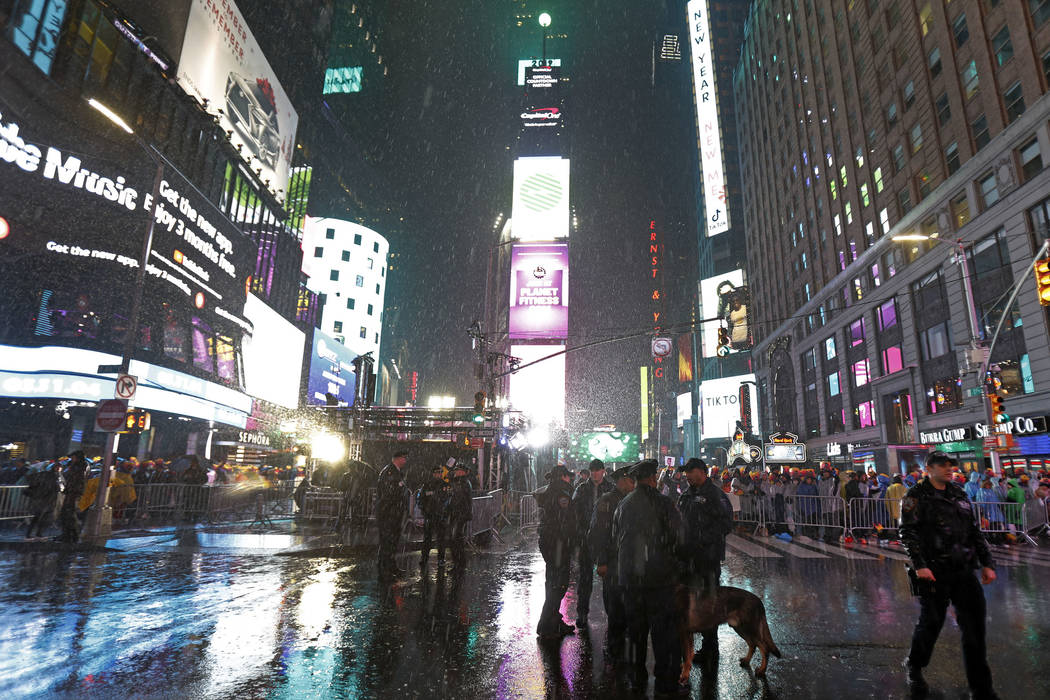 New York City canine police officers stand near revelers gathered in Times Square as rain falls in New York on Monday, Dec. 31, 2018, as they take part in a New Year's Eve celebration. (AP Photo/A ...