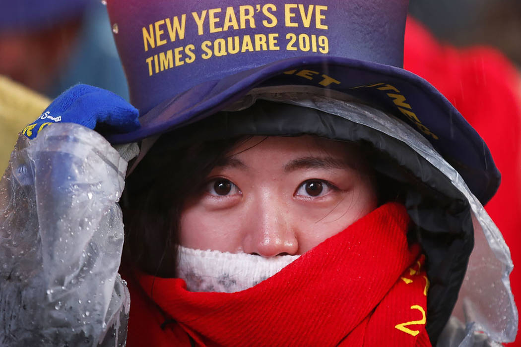 A reveler adjusts her hat as she waits in Times Square in New York on Monday, Dec. 31, 2018, while taking part in a New Year's Eve celebration. (AP Photo/Adam Hunger)