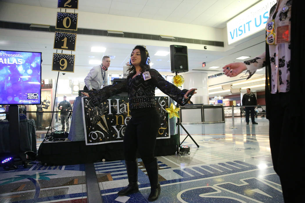 Airport contract specialist Sabrina Khater participates in the silent disco dance party during a New Year's Eve celebration at McCarran International Airport in Las Vegas, Monday, Dec. 31, ...