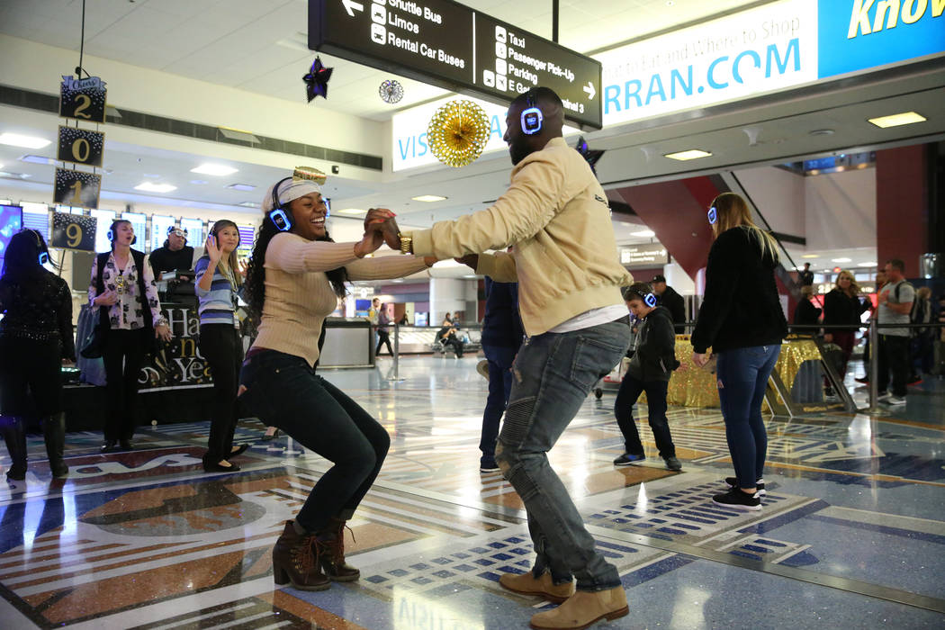Passengers Darious Styles, left, and Quantavia Love, arriving from Miami, dance in the silent disco dance party during a New Year's Eve celebration at McCarran International Airport in Las Vegas, ...