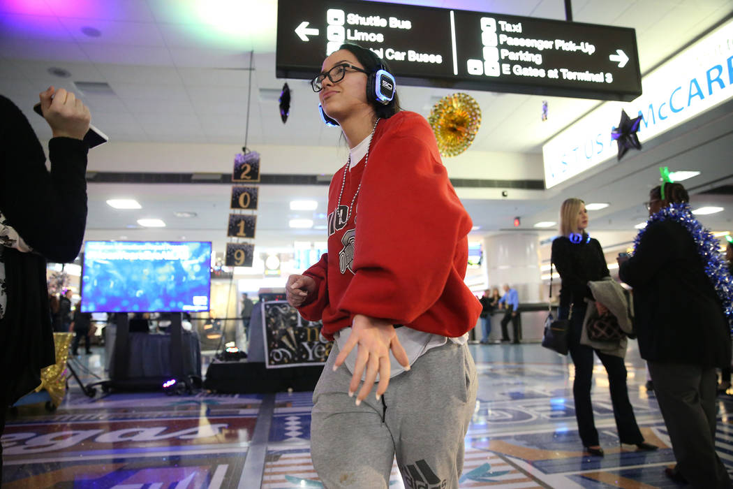 Passenger Anissa Godina, arriving from Washington, dances in the silent disco dance party during a New Year's Eve celebration at McCarran International Airport in Las Vegas, Monday, Dec. 31 ...