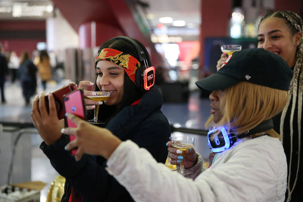 Passengers Mahidiah Caraway, from left, Latisha Robinson, and Sarina Rodriguez, arriving from New Jersey, take a photo during a New Year's Eve celebration at McCarran International Airport in Las ...