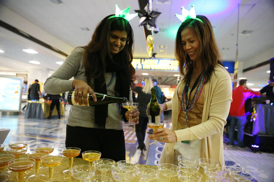 Airport financial office specialists Dianne Yozamp, left, Nataline Bellamy, serve sparkling cider during a New Year's Eve celebration at McCarran International Airport in Las Vegas, Monday, Dec. 3 ...