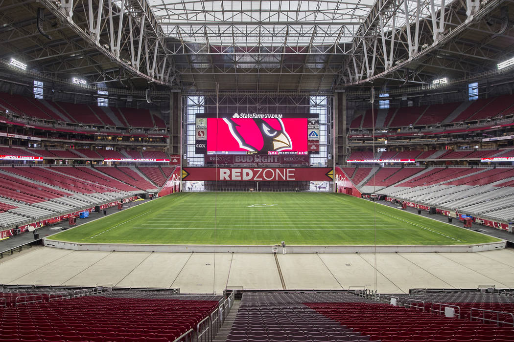 Engineer Don Kramer, middle, oversees the installation of the grass field tray system in preparation for the Phoenix Cardinals NFL football game at State Farm Stadium on Friday, Dec. 21, 2018, in ...