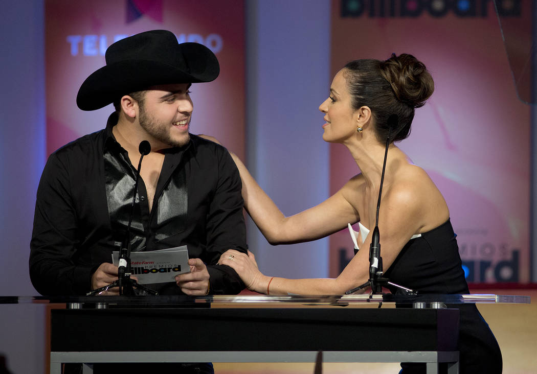 Gerardo Ortiz, left, and Catherine Siachoque announce finalists at the Premios Billboard de la Music Latin press conference in Miami, Tuesday, Feb. 5, 2013. After leading the 2012 list of finalist ...