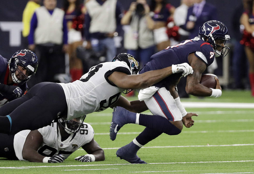 Houston Texans quarterback Deshaun Watson (4) is grabbed by Jacksonville Jaguars defensive end Calais Campbell (93) during the second half of an NFL football game, Sunday, Dec. 30, 2018, in Housto ...
